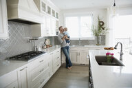 Affectionate father holding and kissing baby son in kitchen - HEROF04135