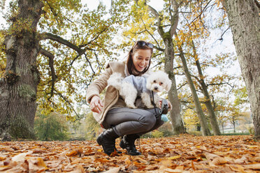 Happy woman with Bichon Frise in forest - ASTF01341