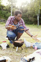 Young man serving grilled sausage in plate during picnic - ASTF01422