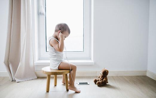 Toddler boy sitting on stool at home using smartphone and earphones - HAPF02808