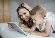 Smiling mother and toddler son lying in bed at home using tablet - HAPF02811