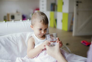 Mother giving glass of water to sick toddler son at home - HAPF02823