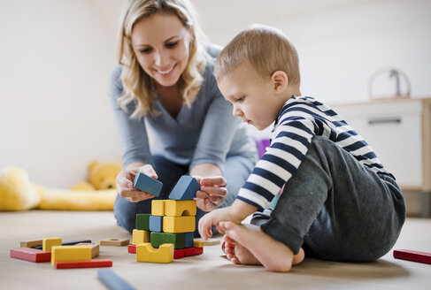 Smiling mother and toddler son playing with building blocks at home - HAPF02826