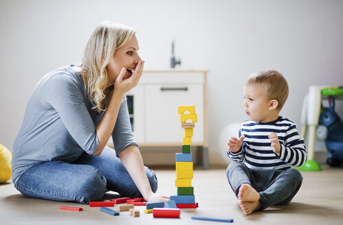 Happy mother and toddler son playing with building blocks at home - HAPF02829