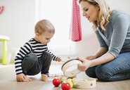 Mother and toddler son playing with musical instruments at home - HAPF02832