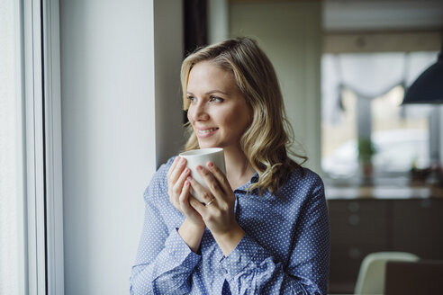 Smiling woman holding a cup of coffee at the window at home - HAPF02844