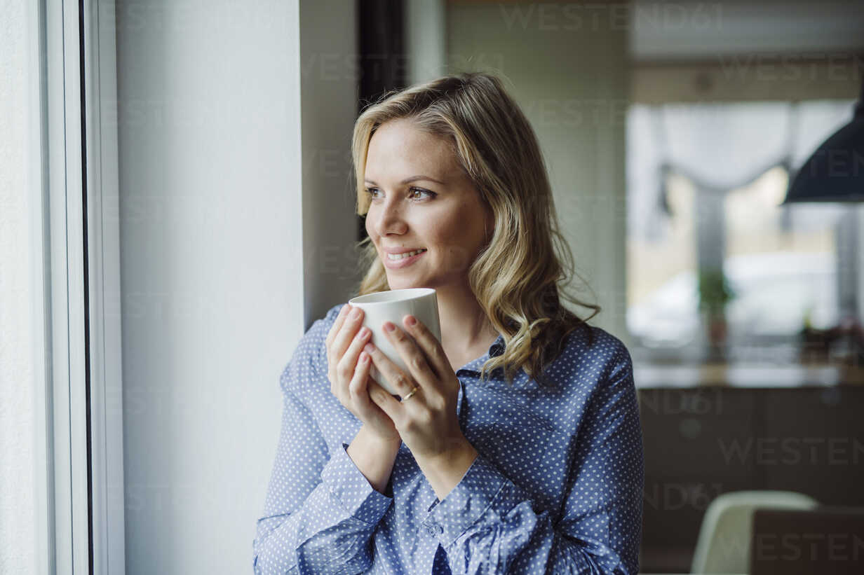 Smiling woman holding a cup of coffee at the window at home - HAPF02844 - HalfPoint/Westend61
