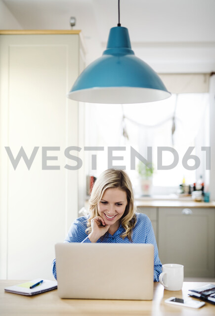 Smiling woman with laptop working at home - HAPF02850 - HalfPoint/Westend61