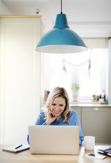 Smiling woman with laptop working at home - HAPF02850