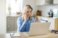 Woman with laptop and cell phone working at home - HAPF02853