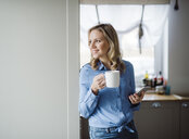Smiling woman holding a cup of coffee and smartphone at home - HAPF02859