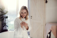 Smiling woman wearing bathrobe in bathroom at home holding cell phone - HAPF02871