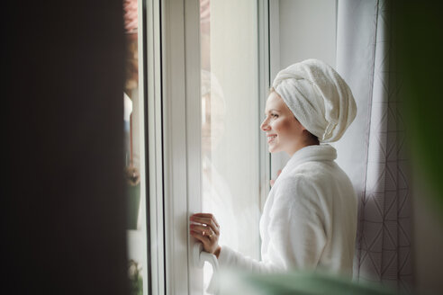 Smiling woman in bathrobe with towel around her head looking out of window at home - HAPF02874