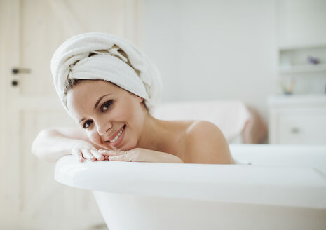 Portrait of smiling woman with towel around her head taking a bath at home - HAPF02877