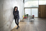 Smiling woman leaning against concrete wall in a loft - FKF03147