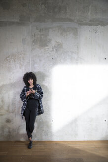 Woman leaning against concrete wall using cell phone - FKF03150
