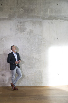 Businessman with cell phone leaning against concrete wall in a loft - FKF03165