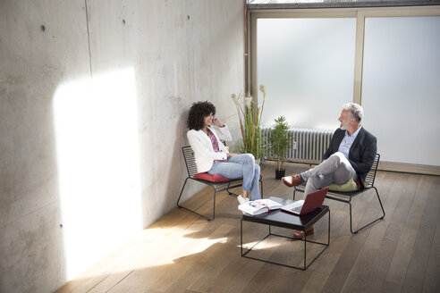 Businessman and businesswoman sitting in a loft at concrete wall talking - FKF03174