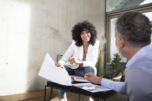 Smiling businesswoman handing over document to colleague in a loft - FKF03180