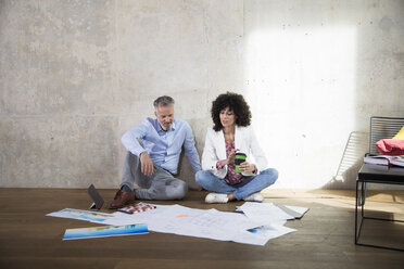 Businessman and businesswoman sitting on the floor in a loft discussing documents - FKF03183