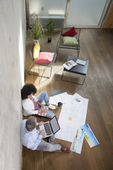 Businessman and businesswoman sitting on the floor in a loft working with laptop and documents - FKF03186