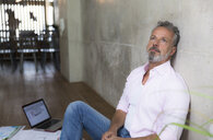Businessman sitting on the floor in a loft having a break - FKF03189