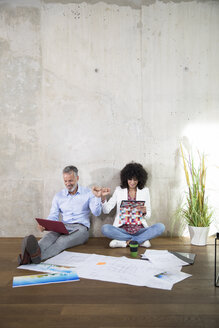 Businessman and businesswoman sitting on the floor in a loft using laptop and tablet - FKF03192