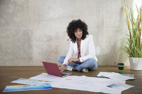 Businesswoman sitting on the floor in a loft working with laptop and documents - FKF03195