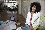 Portrait of smiling businesswoman sitting on the floor in a loft surrounded by documents - FKF03201