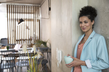 Smiling businesswoman holding coffee mug at concrete wall in a loft - FKF03213