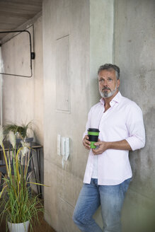 Businessman holding coffee mug at concrete wall in a loft - FKF03216