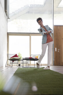 Businesswoman playing golf on artificial turf in a loft - FKF03219