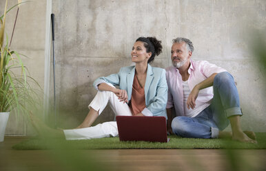 Casual businessman and businesswoman sitting on artificial turf in a loft sharing laptop - FKF03222