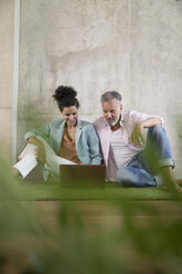 Casual businessman and businesswoman sitting on artificial turf in a loft sharing laptop - FKF03225