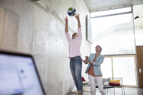 Happy casual businessman and businesswoman playing basketball in a loft - FKF03231