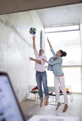 Casual businessman and businesswoman playing basketball in a loft - FKF03234
