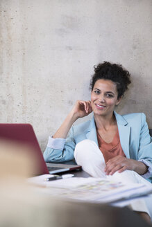 Portrait of smiling businesswoman sitting at table with documents and laptop - FKF03237