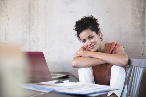 Portrait of smiling businesswoman sitting at table with documents and laptop - FKF03240