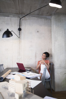 Portrait of smiling businesswoman sitting at table in a loft with documents and laptop - FKF03243