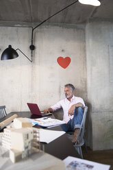 Businessman in a loft using laptop with documents and architectural model on table and heart on the wall - FKF03246