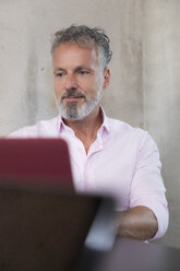 Portrait of businessman using laptop at concrete wall - FKF03249