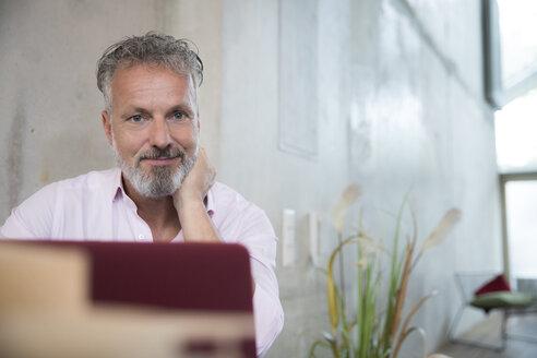 Portrait of confident businessman in a loft using laptop - FKF03252
