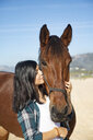 Spain, Tarifa, woman cuddling with horse on the beach - KBF00378