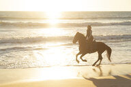 Spain, Tarifa, woman riding horse on the beach at sunset - KBF00387