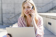 Portrait of smiling blond young woman with laptop on the phone outdoors - GIOF05458