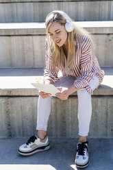 Portrait of blond young woman sitting on stairs outdoors using digital tablet and headphones - GIOF05461