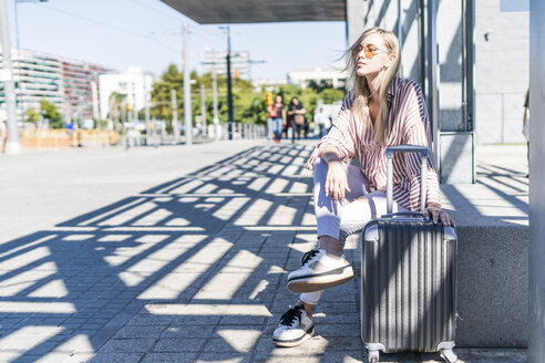 Spain, Barcelona, young woman with trolley bag waiting at station - GIOF05467