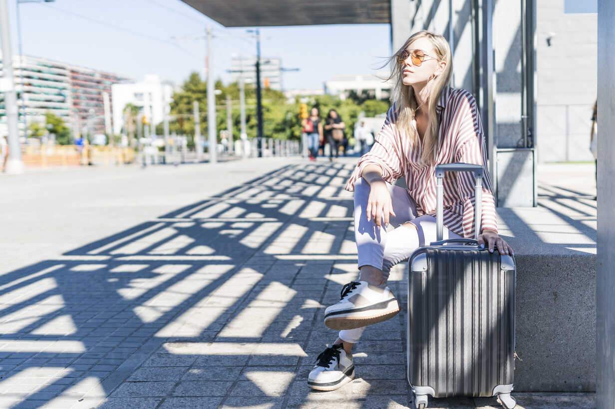 Spain, Barcelona, young woman with trolley bag waiting at station - GIOF05467 - Giorgio Fochesato/Westend61