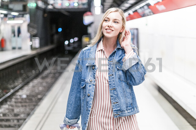 Spain, Barcelona, portrait of smiling young woman with trolley bag at - GIOF05473