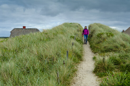 Denmark, Jutland, Henne Strand, woman walking in dunes - UMF00866